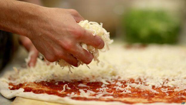 poniendo-mozzarella-a-la-pizza